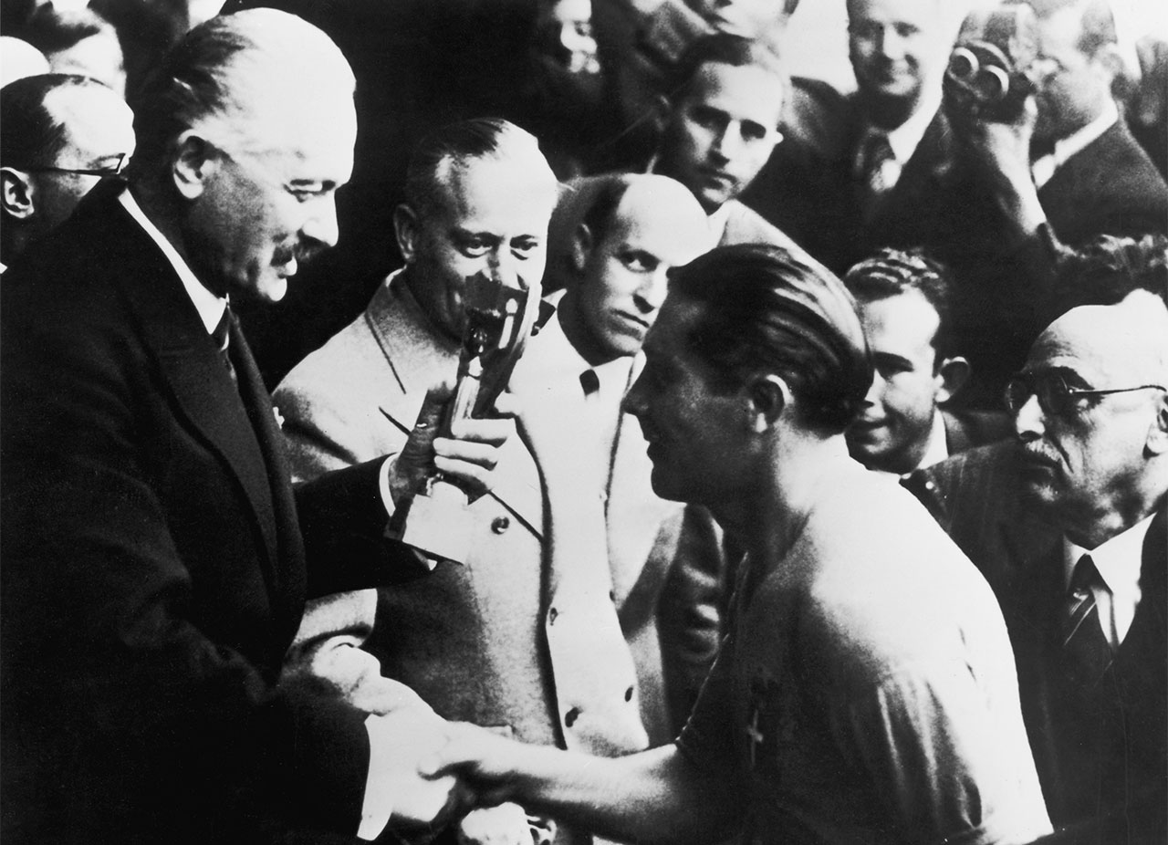 Italy team captain Giuseppe Meazza receives the Jules Rimet Trophy from the President of France, Albert Lebrun, following Italy's win against Hungary in the 1938 World Cup final, Paris